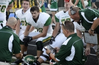 Junior Clay Miller, senior Bradley Philpot, and senior Anthony Hodge meet with head coach Brian Glesing after a scoring drive. Photo by Braden Schroeder