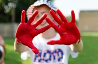 Junior Ryan Shean coats his hands in paint to leave red hand prints on others at the FC vs Providence High School football game.
