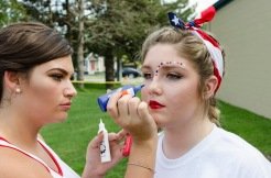 Senior Shelby Stein paints senior Grace Philip's face with red, white, and blue dots.