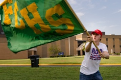 Senior Chandler Stumler waves a FCHS flag at the tailgate shortly before the Kilt Crew heads to the field.