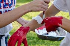 Senior Maci Korfhage paints junior Ryan Shean's arms with white strips.