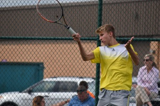 Junior Kyle Poe hits the tennis ball across the court.