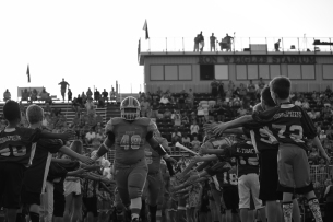 Senior Donovan Hickman leads the Highlanders out of the fan-made tunnel before kickoff against Columbus East.