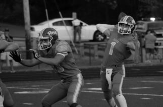 Junior Jason Cunfiff protects junior Matt Weimer as he makes a pass attempt.