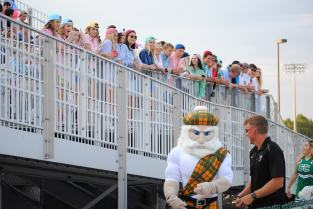 Micah Willcher leads sophomore Gabe Jones, who is dressed as the Highlander mascot, past the student section.