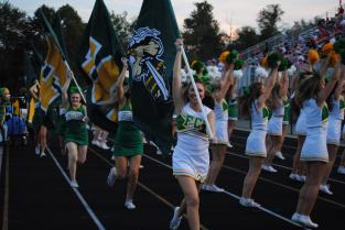Lead by junior Claire Wheeler, the cheerleaders run in front of the stadium after FC scores a touchdown.