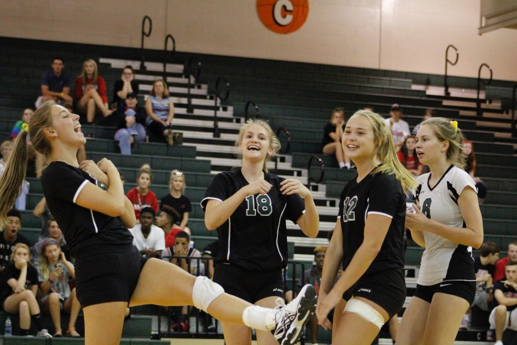 Seniors Taylor Hodges, Kendall Hoback , junior Kristen Engle, and sophomore Sara Sans celebrate after Hodges got a kill. A kill is when a player makes a pass directly scoring a legal, non returnable point. Photo by Gabriel Pauly.