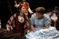 Sophomore Elizabeth Hallal and senior Emily Hardin sit together onstage.