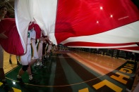 Members of both basketball teams hold the flag during the National Anthem.