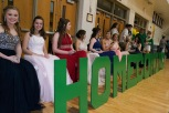 Members of homecoming court sit under the basket watching the game.
