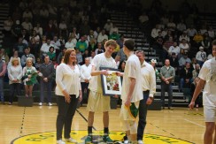 Senior Trevor Apple with parents Heather and Jeffrey Apple receive gifts from junior Brendan Hobson. Photo by Kaitlyn Erdman.