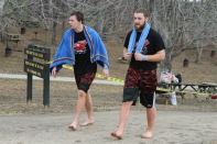 Seniors Trevor Clark and Chas Adams walk out of the water towards the changing area after enduring the frigid water. Photo by Miranda Legg.