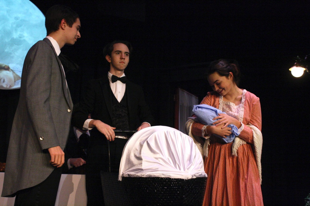 Pennington delivers a child to Burger and Bowers. Pennington represents the concept of time in the play, and comes on stage several times to either bring new life or take the old away.