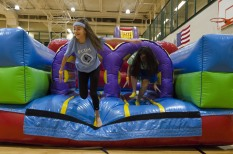 Freshmen Olivia Stinson and Sydney Wallace jump out of a blow-up obstacle during the first FCDM breakout session. Photo by Robert Wormley