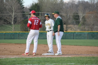 Senior Brayden Edwards stands on first base talking to assistant coach Jamie Polk.