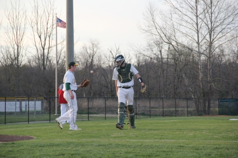 Senior Jon Cato tosses the ball to senior Chase Stepp as he comes onto the field.