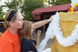 Arnold helps her daughter, Bella, decorate the cake. They continue to add bright tinsel to the float, spicing it up.