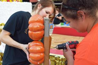 Volunteers Haley Matheny and Lewis screw pumpkins into a wooden board. The board is mounted onto the sides of the float, setting the mood for the fall season.
