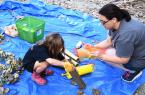 """Volunteer Kia Black shows Bella how to stuff the candle """"flames"""" into the cardboard base."""