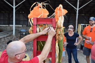 Koch zip ties scarecrows to the back of the float. They cover up the tracks used to load vehicles onto the trailer on other days of the year.