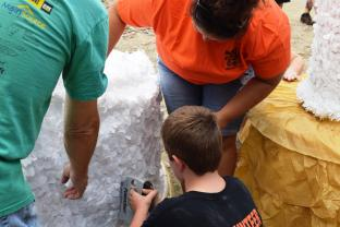 Volunteer Courtney Lewis watches as junior volunteer Tristan Arnold staples on decorations. They are designing a fake cake to put on the Harvest Home Coming float in the parade next Saturday.