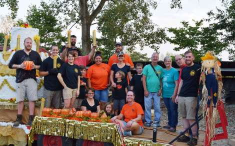 Everyone on the Harvest Homecoming float decorating crew poses together with smiles bright and attitudes positive. They hope to win the float contest, but mostly are just glad to have fun doing it.