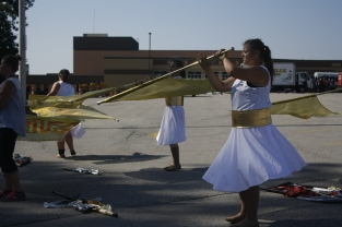 """Eastern High School senior Makayla Shepherd spins her flag during physical warm up. Eastern High School is from Pekin, Indiana and is one of the 18 bands that traveled to FC to compete. """"I like being able to pursue music visually and I enjoy being able to put emotion and feeling into color guard,"""" said Shepherd."""