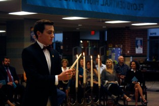 Senior Tux Tuxworth, NHS president, lights the final candle during the fall induction program. Each candle represents a pillar of NHS and over the course of the program each officer lit a candle.