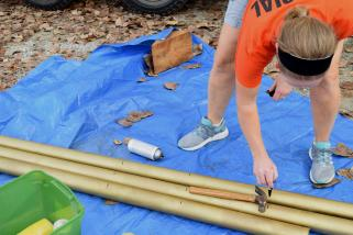Volunteer Mary Arnold uses a hammer to measure the candles for the cake model. After being spray painted gold, for the 50th anniversary of Harvest Home Coming, the cardboard mock-candles are nearly ready to be added to the float.