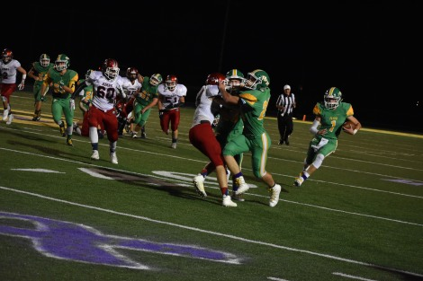 Senior Matt Weimer and the rest of the offense run a play against Bedford. Players ran, tackled, and blocked during the exiting play, which resulted in plenty of gain for FC. Photo by Tori Roberts.
