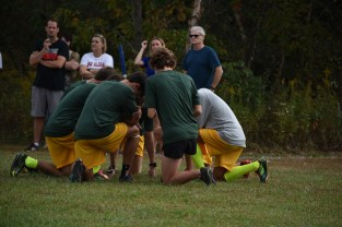 The boys' cross country team kneels together briefly before running. They kneel down before every race, allowing them to clear their minds before they run. Photo by Tori Roberts.