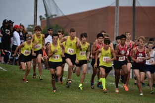 Boys' cross country strides past the starting line of the race. The course, like most high school cross country meets, is 5 kilometers(3.1 miles) long. Photo by Tori Roberts.