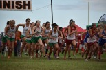 The entire girls' cross country team jolts forward at the sound of the gunshot that signals the start of the race. Surrounded by rival teams of girls, they stride foreword towards the front at the very start of the race. Photo by Tori Roberts.