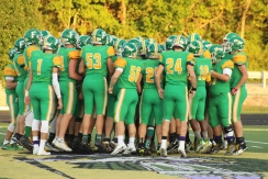 The FC football team gathers in the center of the field to pump up each other before the game begins against Bedford North Lawrence. Photo by Taylor Watt.