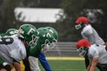 FC's offensive line gets into position during a team scrimmage. The players wore red scrimmage caps to separate the defense from the offense. Photo by Tori Roberts.