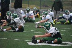 The entire football team lines up in rows and stretches together. Stretching as a team not only makes the players more flexible, but brings them together as a unit. Photo by Tori Roberts.