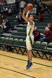 Junior Harrison Eades hops for a three-pointer when warming up before the JV game against New Albany. Even before the main event, more than 100 fans had shown up to support their teams. Photo by Tori Roberts.