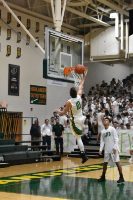 Sophomore Seth Burks goes for a layup in the warmups before the varsity game. Even before the game started, fans crowded the stands to cheer for their respective teams. Photo by Tori Roberts.