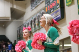 Junior Makenna Moravec smiles and cheers on the sidelines towards the end of the second quarter of the game. Photo by Taylor Watt.