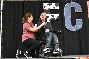 Alumni Kristen Burger and Caleb Lammert walk on stage for Lammert to tell his own Riley story.