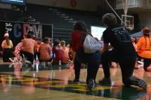 Students kneel as former FC teacher Delbert Hillegas tells his Riley story.