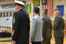 Principal Rob Willman, lieutenant colonel Vandermeer, and Gunner Epperson rise during the performance of the national anthem.