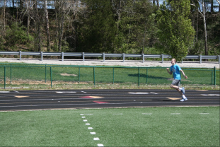 Freshman Avery Campbell leads his team in the warm up laps around the track at practice on April 30. Photo by Sophia Perigo