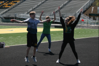 "Mac Deluca and Senior Delaney Mazza lead this kids in their warm up. "" The kids on unified track team help me more than I could ever help them! Since I started helping in their classroom and on the track team they have all become some of my best friends and favorite people to talk to. They never fail to put a smile on my face!"" said Mazza. Photo by Sophia Perigo"