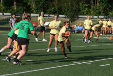 """Junior Katie Yankey runs the ball down the field and maneuvers to keep her flags from getting pulled. """"When you have the ball, you're just trying to go as fast as you can and as far as you can,"""" said Yankey. Photo by Sophia Perigo."""