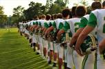 """The boys' football team stand in a single file line with their hands over their hearts while listening to the National Anthem before the Floyd vs. Charlestown scrimmage. """"My favorite thing about football is being able to play the sport I love with all my best friends,"""" said senior Brett May. Photo by Grace Allen."""