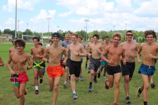 "The whole boys' cross country team runs towards the camera during practice. ""The main reason I do cross country is to be in shape for track season later on in the year,"" said junior Talon Hutto. Photo by Grace Allen."
