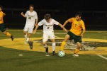 """Junior Xander Ochsner fights to get the ball away from an opposing player so he can get to the goal. """"I love the guys that I play with and it's better with a group of people,"""" said Ochsner. Photo by Grace Allen."""