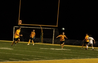Junior Xander Ochsner heads the ball to his teammate to get it moving in the other direction. Photo by Grace Allen.