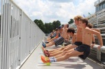 The boys do dips on the bleachers during their warm-up before practice. Photo by Grace Allen.